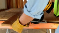Closeup shot of construction workers sawing board video