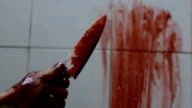 Closeup shot of hand holding a bloody knife with blood dripping video