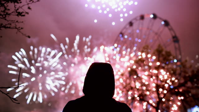 Closeup silhouette of alone man watching fireworks on new year celebration outdoors video