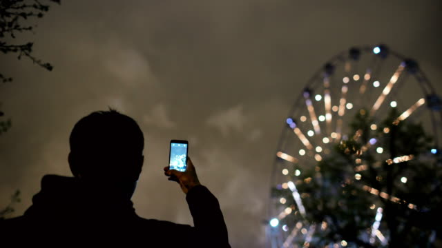 Closeup silhouette of man watching and photographing fireworks explode on smartphone camera outdoors video