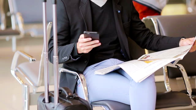 Closeup smartphone in male hands and newspaper inside in airport. Casual young businessman wearing suit jacket. Young man with cellphone at the airport while waiting for boarding video