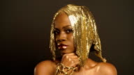 Close-up Surreal Portrait of Glossy African American Woman with Bright Golden Makeup and Headwear. Bronze Bodypaint video