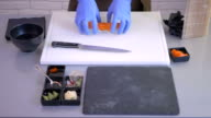 Close-up - the cook forming a sushi roll from a small pieces on a board video