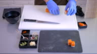 Close-up - the cook put a small pieces of sushi on a black square plate video