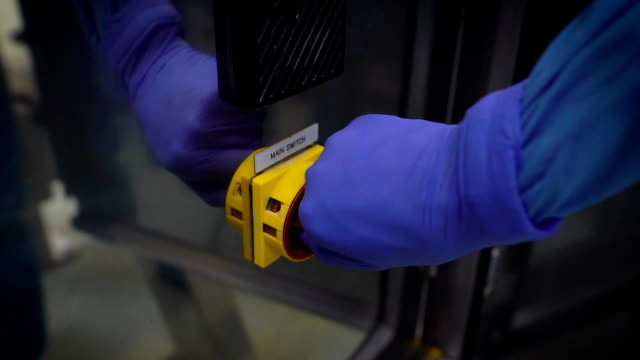 Close-up. The worker in gloves includes the main switch of equipment, installation. A large red switch that provides power to an automatic line in production video