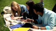 Closeup three students reading tutorial outdoors video