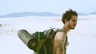 Closeup video of the young tattooed Caucasian man, tourist - hiker with the big backpack, walking through the sandy desert. White Sands National Monument, New Mexico, USA. video