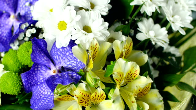close-up, view from above, Flower bouquet in the rays of light, rotation, the floral composition consists of Alstroemeria, Chrysanthemum bacardi, Orchid vanda, Santini , gypsophila, Eustoma video