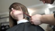 Closeup view of a hairdresser's hands cutting hair with scissors. Hairdresser at work. Beauty saloon. Shot in slowmotion video