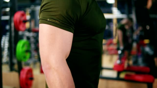 Closeup view of a sporty man's strong hand doing dumbell curl exercises in gym. Shot in 4K video