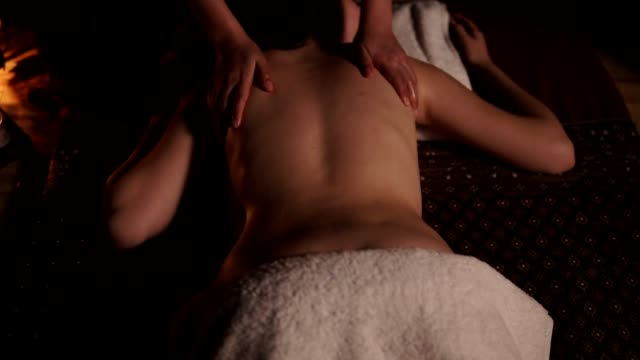 Closeup view of a young woman's oiled back having thai massage in spa by a female massagist in kimono. Slowmotion shot video