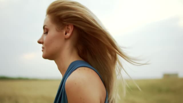 Closeup view of attractive young blond woman in a blue dress walking through golden wheat field. Freedom concept. Slowmotion shot video