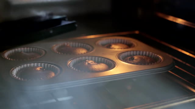 Close-up view of baking dish with chocolate cupcakes. Time lapse of growing of the dough, muffins in baking tray video