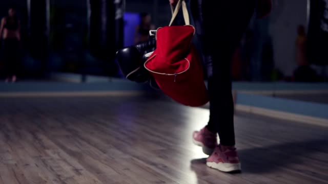 Closeup view of legs of young fit woman entering a fitness club with a bag and boxing gloves and preparing for the training in a boxing club. video