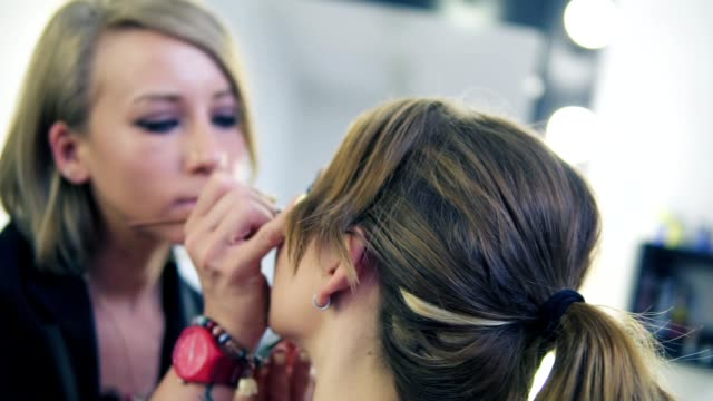 Closeup view of makeup artist applying eyeshadow on eyelid using makeup brush. Professional makeup. Slowmotion shot video