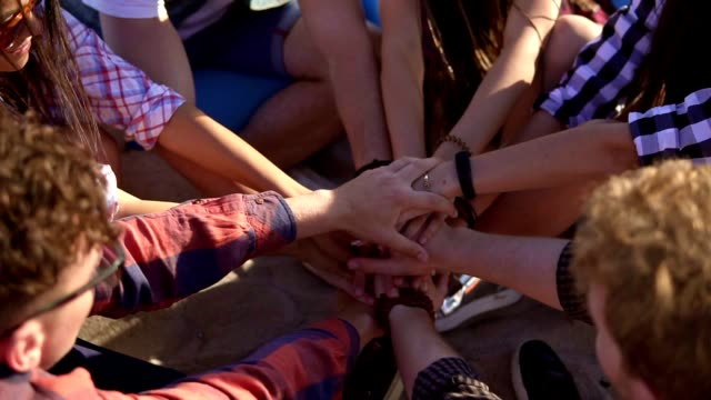 Closeup view of many hands united together and raised up. Teamwork and friendship concept. Group of friends sitting on easychairs on the beach on a summer evening. Slowmotion shot video
