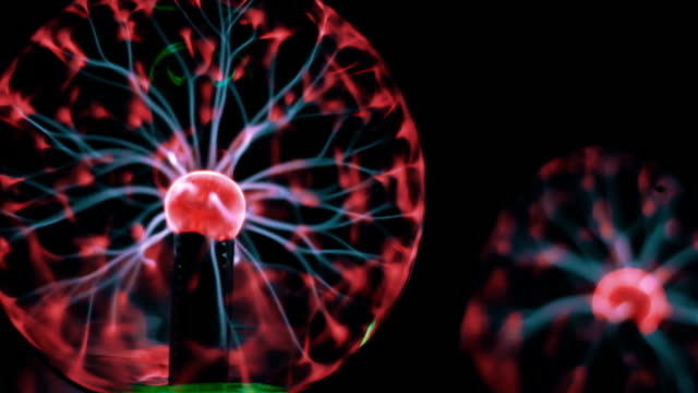 Closeup view of plasma ball with moving energy rays inside on black background video