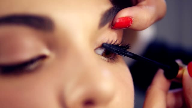Closeup view of professional makeup artist applying mascara on the model's eyelashes. Work in beauty fashion industry. Backstage professional make-up video