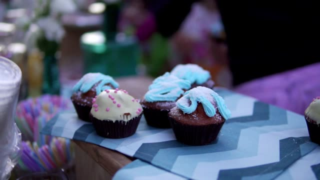 Closeup view of sweet decorated cakes and muffins standing on the table. All the muffins are different in shape and color. Cupcakes on the table during the party video