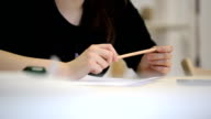 Close-up view of woman holding pencil and talking video