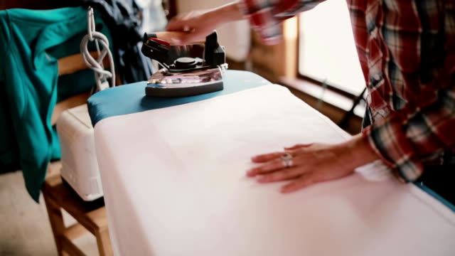 Close-up view of woman ironing clothing or sheets on the iron board. Domestic homework for a housewife video