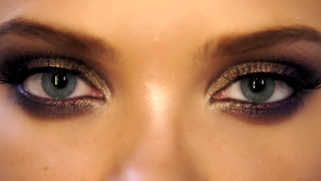 Closeup view of woman's eyes with beautiful golden makeup opening and closing in slowmotion video