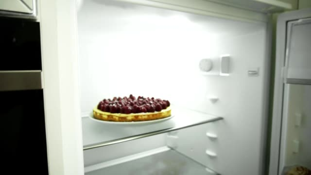 Closeup view of woman's hands coming to the fridge, opening the door and taking out the plate with the cake decorated with raspberries. Homemade cake. Party preparation video