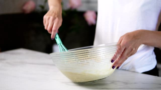 Closeup view of woman's hands mixing ingredients to prepare dough in the the bowl using whisk. Home cooking. Slowmotion shot video