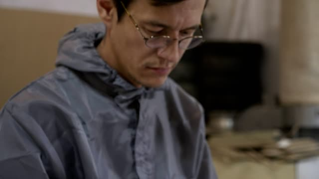 Closeup view of young adult man worker in a glasses using smart phone at factory video
