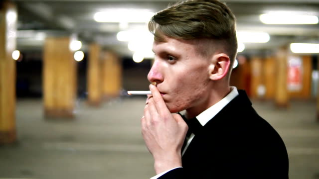 Closeup view of young blonde man in a black suit with a bow-tie smoking a cigarette in the parking. Waiting for someone. video