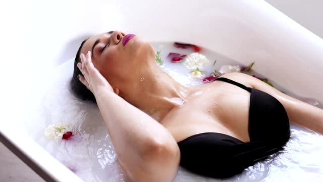 Closeup view of young woman bathing in milk bath filled with flowers and getting up. Spa and skin care concept. Slowmotion shot video