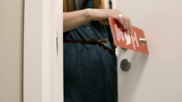 Close-up view of young woman comes out from the room in hotel and puts on knob the door hanger, asking do not disturb video