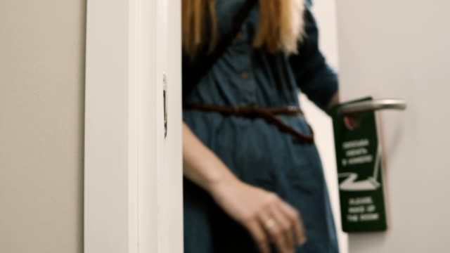 Close-up view of young woman comes out from the room in hotel and puts on knob the door hanger, asking to clean the room video