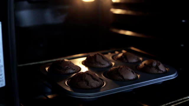 Close-up view of young woman opens the oven and gets out the baking tray for cupcakes. Female cooking the desserts video