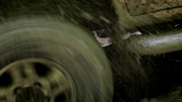 Close-up wheel of SUV got stuk in mud and slips with splash of water and mud. video
