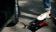 Closeup woman's foot inflating car tyre with pump video