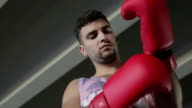 Close-up. Young boxer takes off red gloves after a workout. video