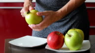 Close-up  young housewife removing apple peel. video