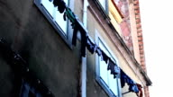 Clothes hanged on the wire the side of a building video