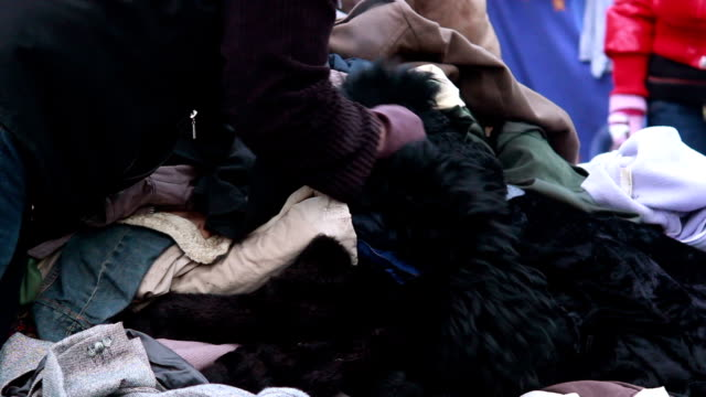 Clothes pile for poor people winter outdoor, male choosing coat video