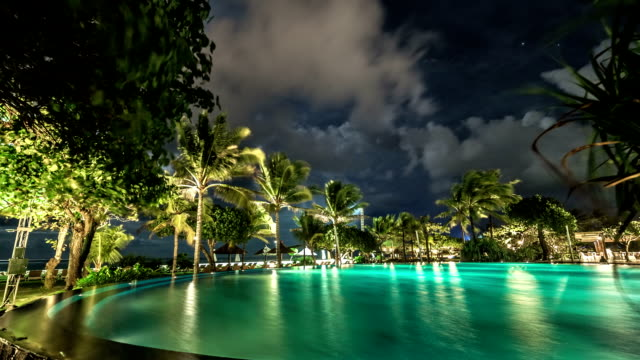 Clouds float above the illuminated night pool against the backdrop of palm trees and the sea. FullHD Timelapse - Bali, Indonesia video