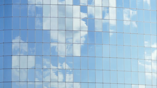 Clouds reflected in windows of modern office building video