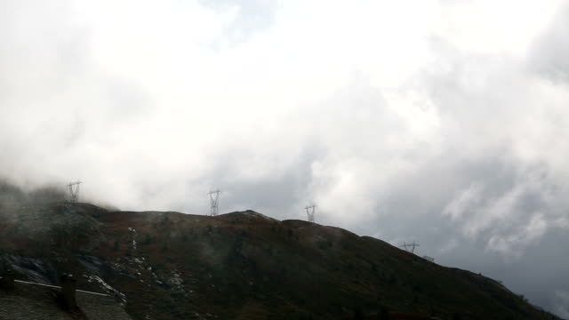 Clouds stream past mountains and power pylons video