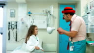 Clown  shows a trick to the girl in hospital video