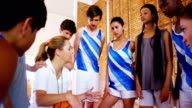 Coach instructing a students in basketball court video