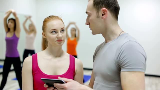 Coach man explaining to girl her fitness training program video