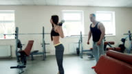 Coach watching sportswoman doing squats with bar video