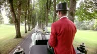 SLO MO Coachman in red uniform driving a horse carriage video