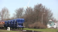 Coal railway cars with a windturbine in the background video
