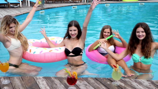 Cocktail party at resort, girlfriends in bathing suit Have fun in Poolside, Laughing girls sitting at Inflatable ring in pool video